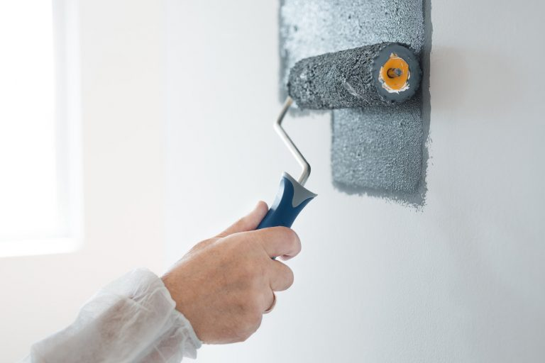 Closeup of renovation crew painting wall grey with painting roll